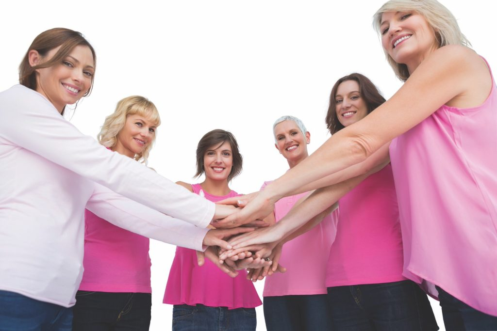 Women posing in circle holding hands wearing pink for breast cancer looking at camera on white background